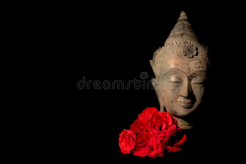 Paix et amour Statue traditionnelle de la tête de Bouddha avec des roses rouges images libres de droits