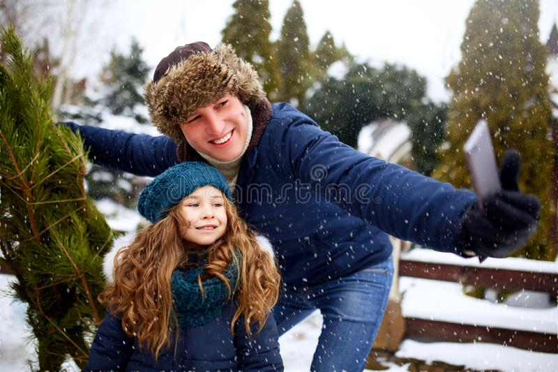 Paizinho bonito e filha que fazem o selfie com a árvore de Natal recentemente cortada com o smartphone perto da casa Família nova foto de stock royalty free