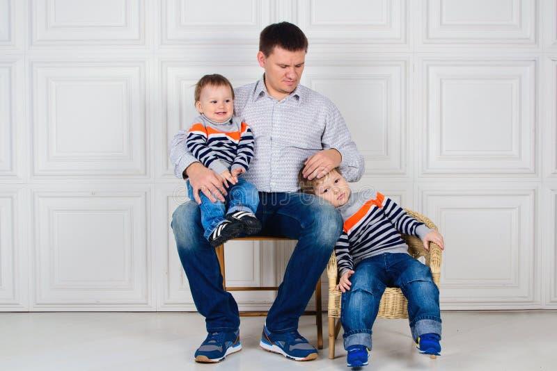 Paizinho com as duas crianças em seus joelhos que sentam-se na cadeira na frente da parede branca lifestyle Crianças em camisetas imagens de stock