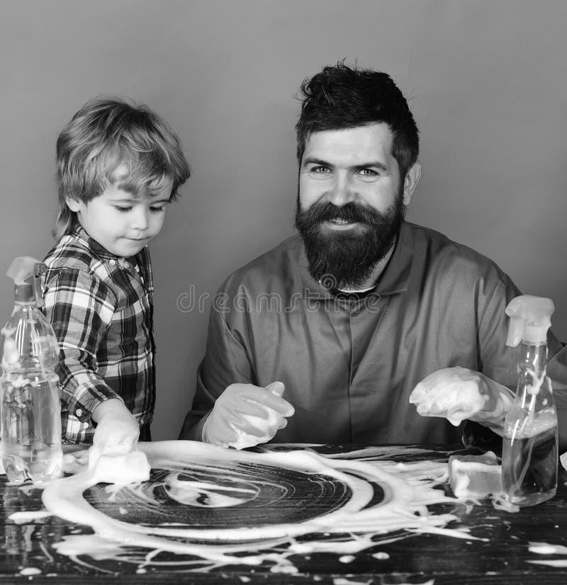 Paizinho com fontes do filho e de limpeza no fundo verde O pai e a criança fizeram a espuma na tabela Conceito do tempo da famíli fotos de stock