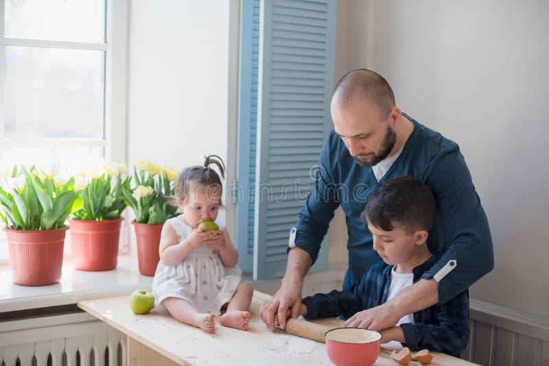 Paizinho com seus filho e filha pequenos que cozem junto imagens de stock