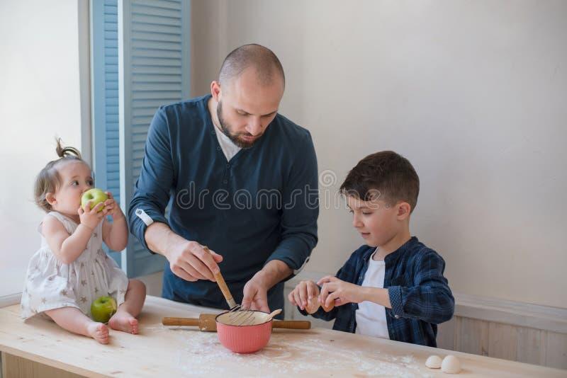 Paizinho com seus filho e filha pequenos que cozem junto fotografia de stock