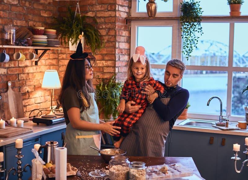 Paizinho da mamã e filha pequena com composição e chapéus que cozinham junto na cozinha do estilo do sótão na manhã imagens de stock