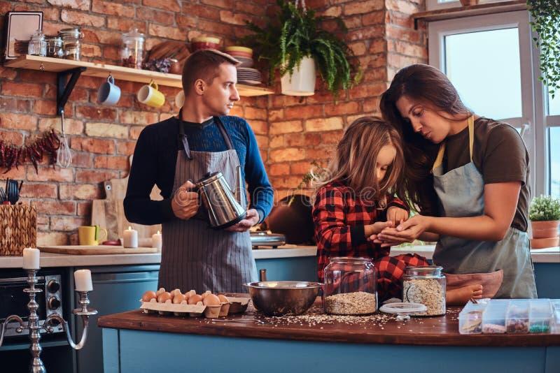 Paizinho da mamã e filha pequena que cozinham junto o café da manhã na cozinha do estilo do sótão fotos de stock royalty free