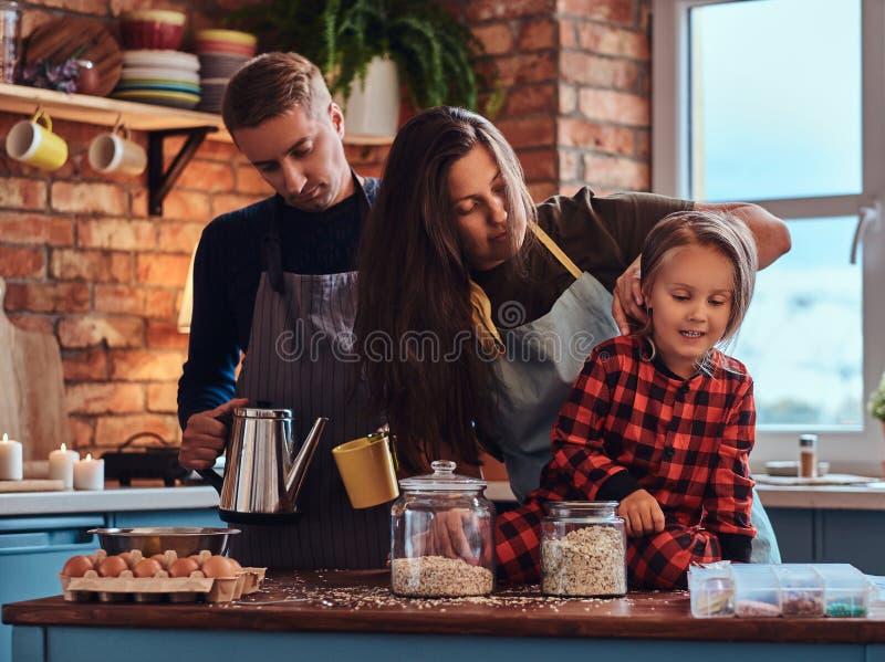 Paizinho da mamã e filha pequena que cozinham junto o café da manhã na cozinha do estilo do sótão imagem de stock royalty free