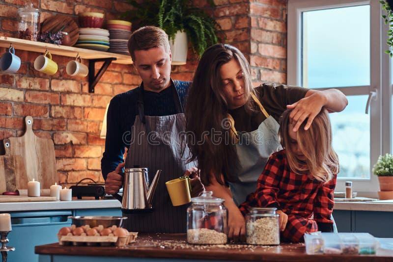 Paizinho da mamã e filha pequena que cozinham junto o café da manhã na cozinha do estilo do sótão imagem de stock