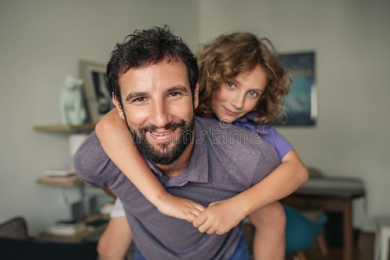 Paizinho de sorriso que dá a seu filho um reboque em casa fotografia de stock