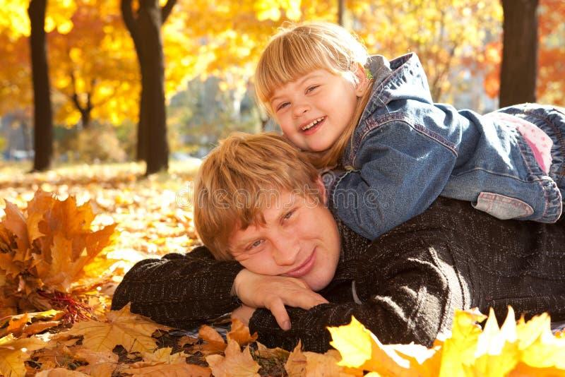 Paizinho e filha nas folhas de outono fotografia de stock