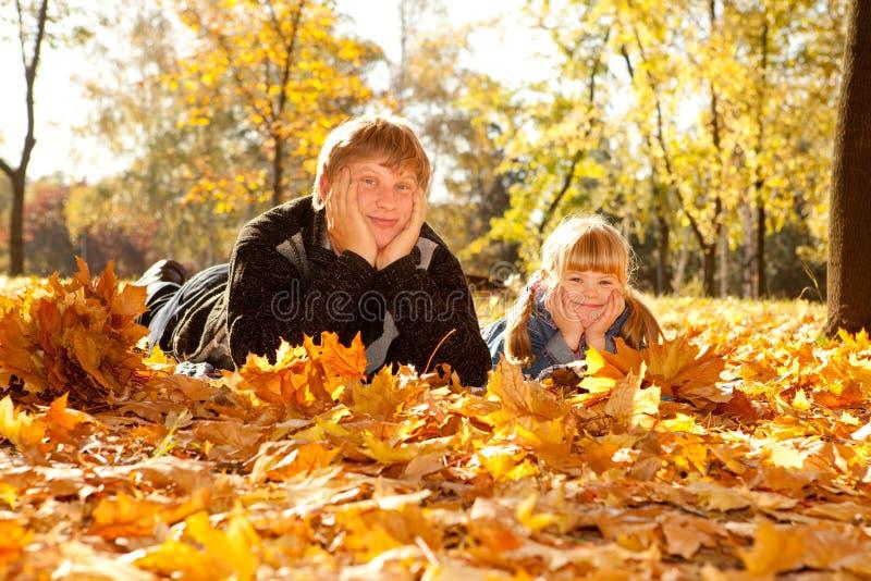 Paizinho e filha nas folhas de outono imagem de stock
