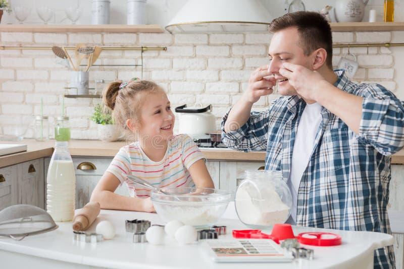 Paizinho e filha que cozem junto na cozinha fotografia de stock royalty free