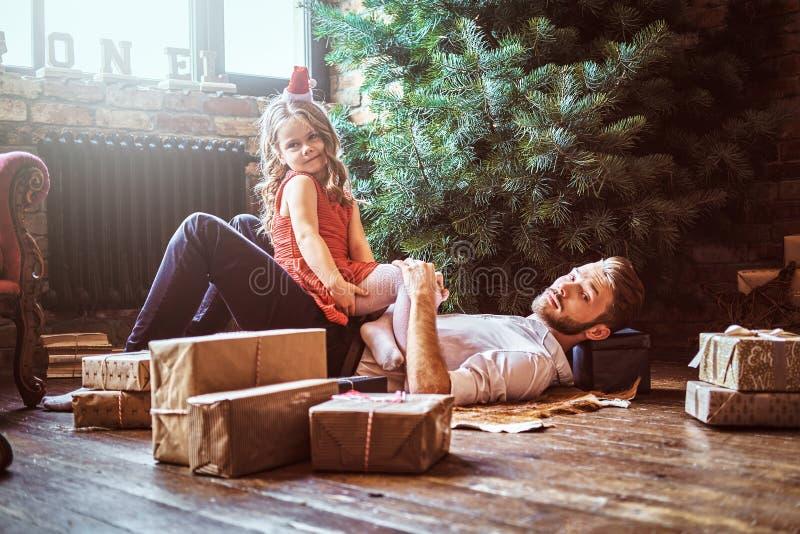 Paizinho e filha que encontram-se no assoalho, cercado por presentes perto da árvore de Natal imagem de stock