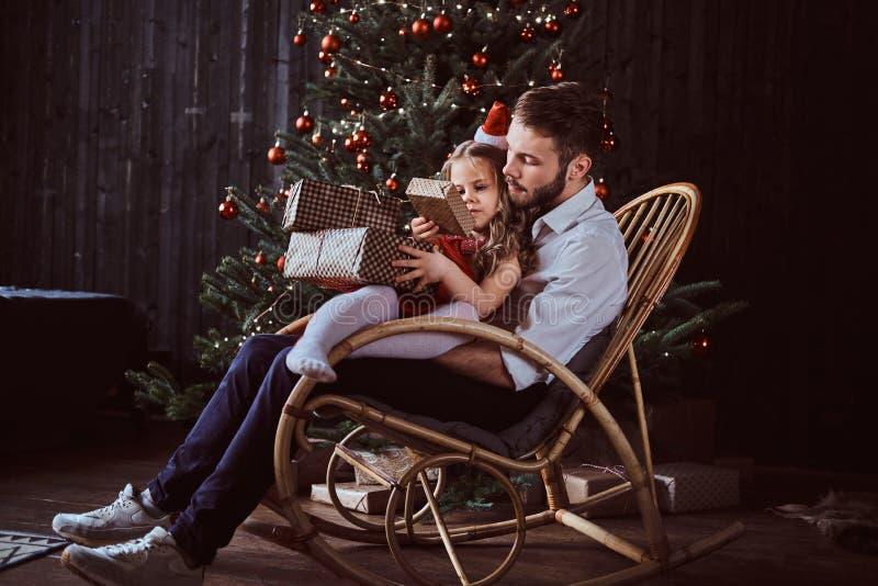 Paizinho e filha que guardam caixas de presente ao sentar-se junto em uma cadeira de balanço perto de uma árvore de Natal em casa imagem de stock royalty free