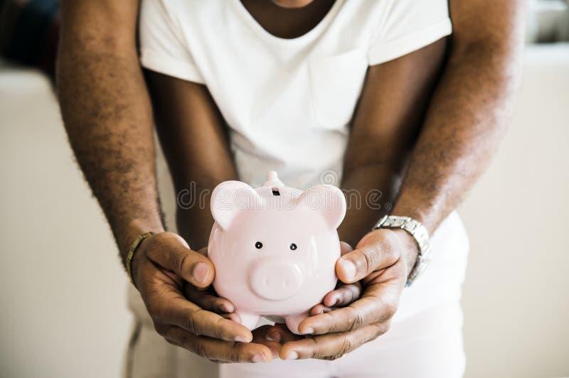 Paizinho e filha que guardam o mealheiro nas mãos imagens de stock royalty free