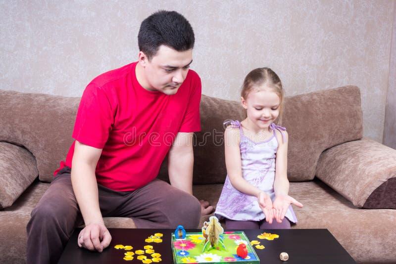 Paizinho e filha que jogam o jogo de tabela imagem de stock royalty free