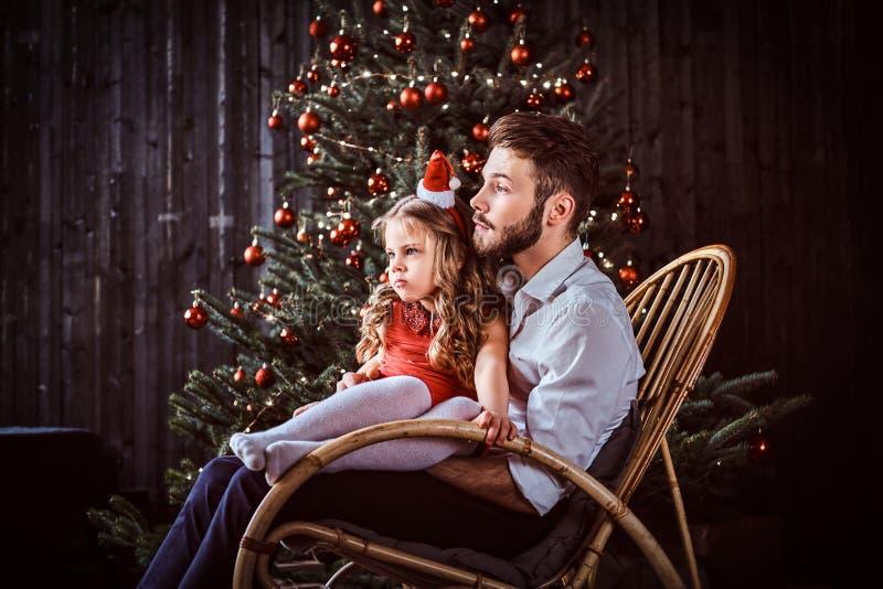 Paizinho e filha que sentam-se junto em uma cadeira de balanço perto de uma árvore de Natal em casa imagem de stock