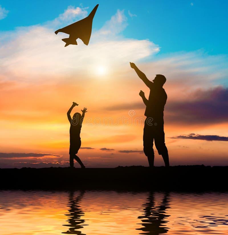 Paizinho e filha que voam um papagaio na praia fotografia de stock
