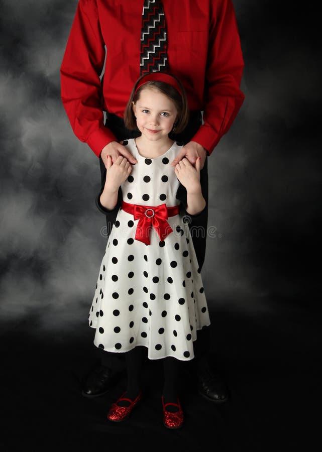 Paizinho e filha vestidos acima das mãos da terra arrendada fotografia de stock royalty free