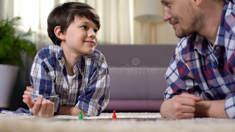 Paizinho e filho que jogam o jogo de mesa, habilidades tornando-se do pensamento lógico, paternidade fotos de stock royalty free