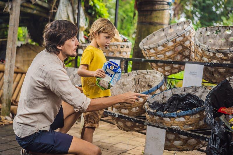 Paizinho e filho, recolha de lixo separada Crianças de ensino para separar a recolha de lixo foto de stock royalty free