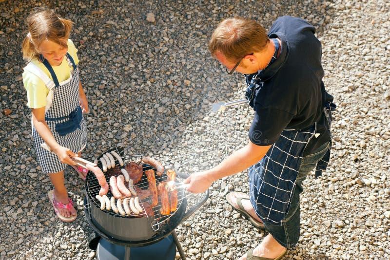 Paizinho e miúdo que fazem o BBQ fotos de stock royalty free