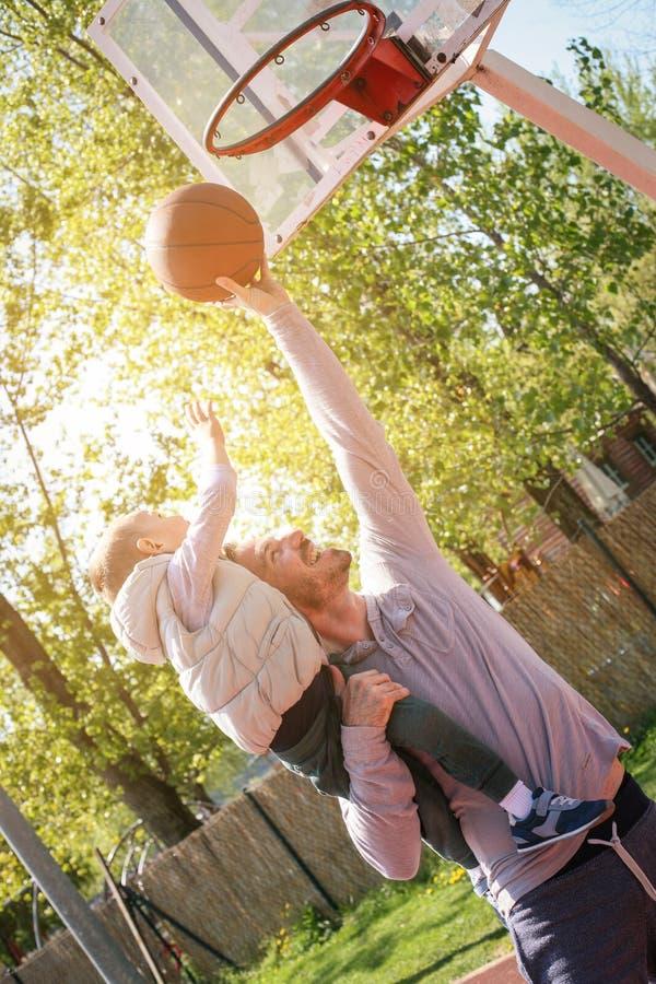 Paizinho e seu filho que jogam o basquetebol junto foto de stock