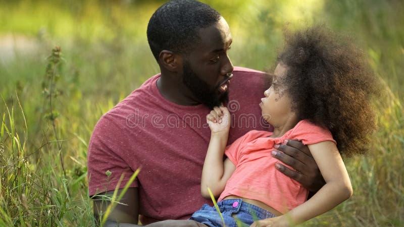 Paizinho engraçado e filha que fazem as caras parvas junto, sentando-se na grama verde imagens de stock royalty free