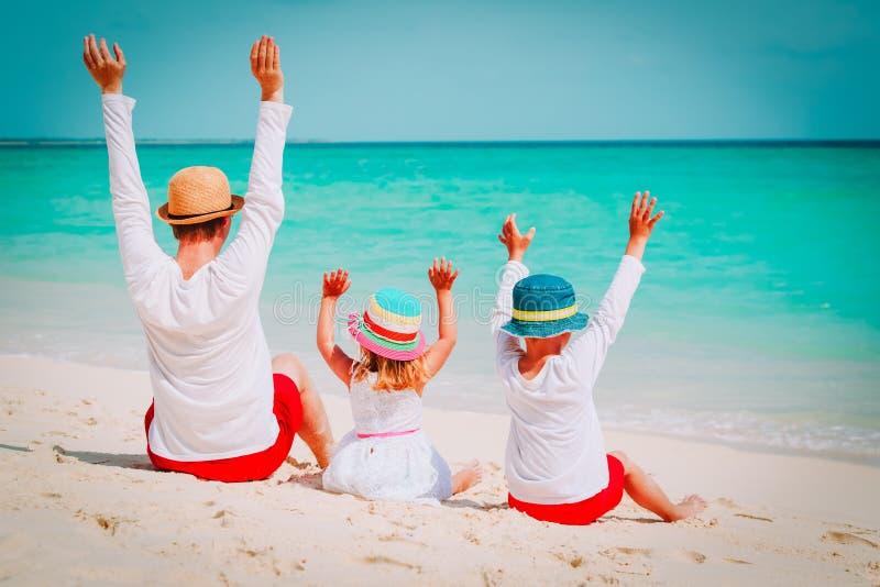 Paizinho feliz com mãos do filho e da filha acima na praia imagens de stock royalty free