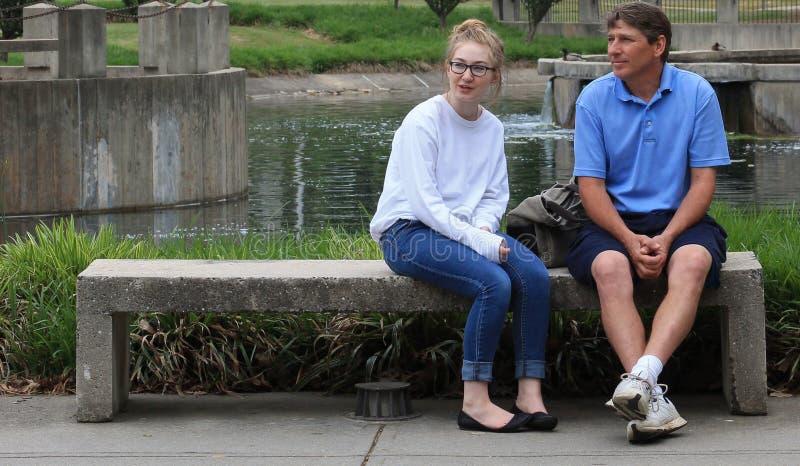 Paizinho/filha no banco de parque fotos de stock royalty free