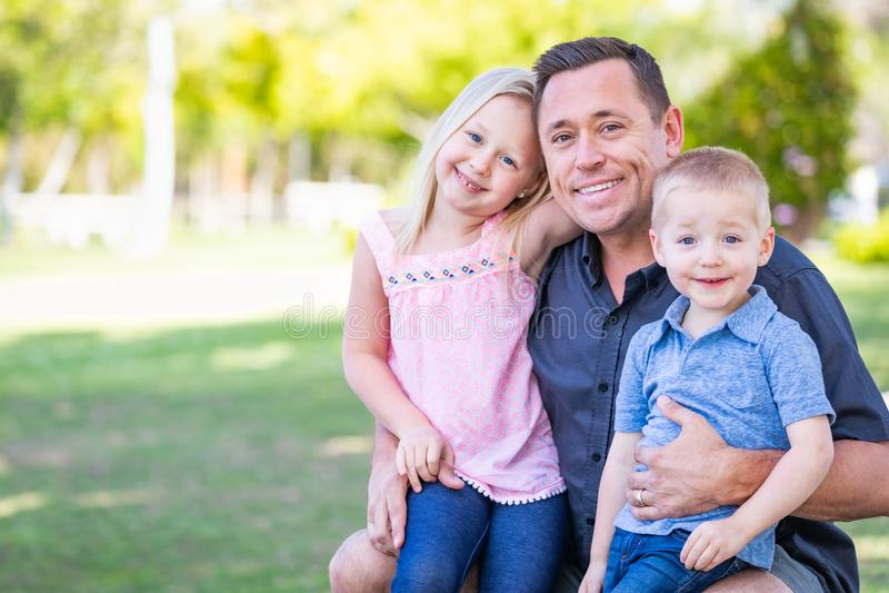Paizinho, filho feliz e filha caucasianos tendo o divertimento no parque foto de stock