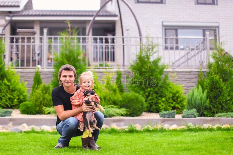 Paizinho novo e sua filha pequena com seu cachorrinho no fundo sua casa imagens de stock