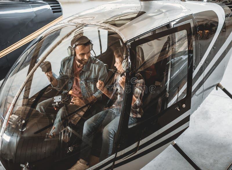 Paizinho otimista que diz com a criança no helicóptero foto de stock royalty free