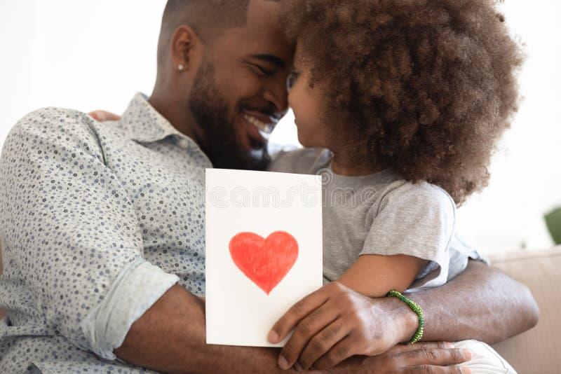 Paizinho preto que abraça o cartão pequeno da terra arrendada da ligação da filha imagem de stock