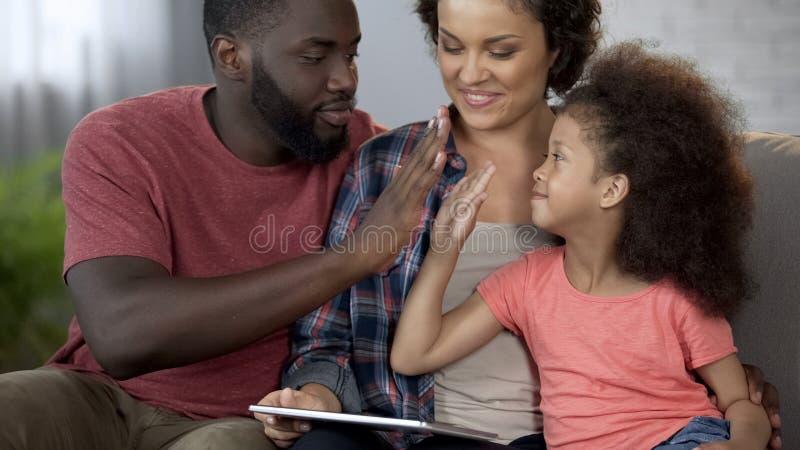 Paizinho preto que dá altamente cinco a pouca filha encaracolado-de cabelo, família junto fotografia de stock royalty free