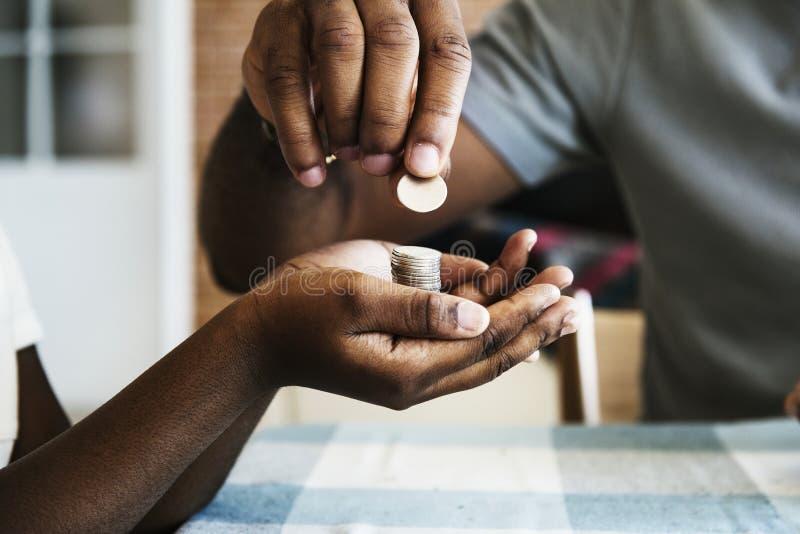 Paizinho que dá moedas a sua filha fotos de stock