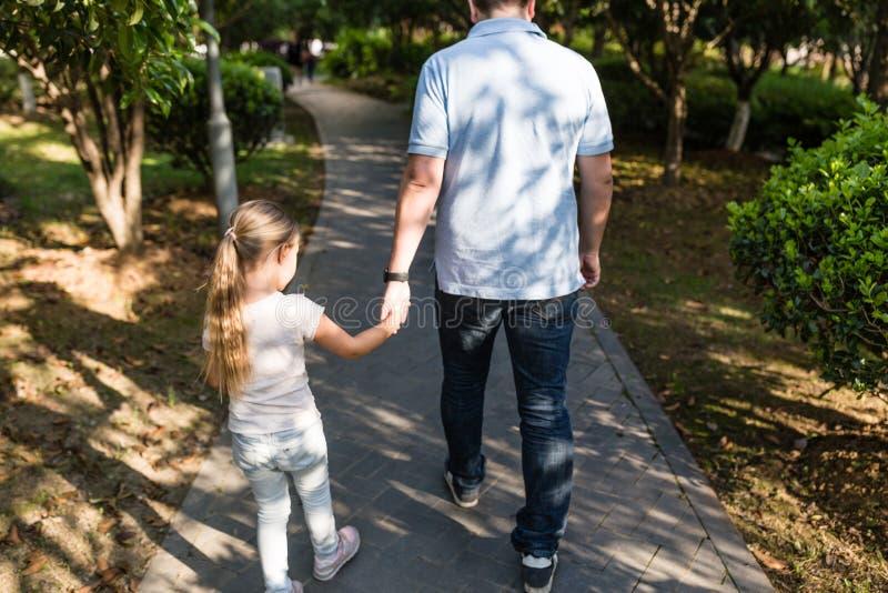Paizinho que guarda a filha das m?os com amor e que anda no parque Conceito de fam?lia fotos de stock royalty free