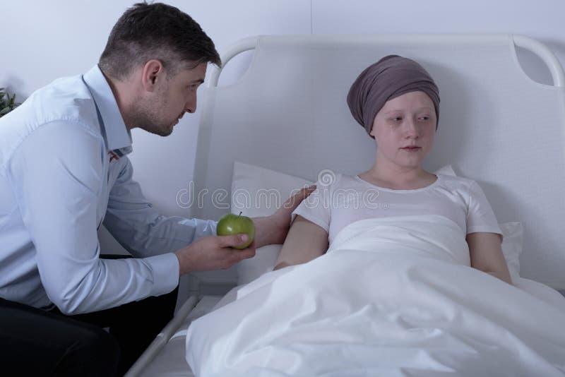 Paizinho que importa-se com a filha doente foto de stock