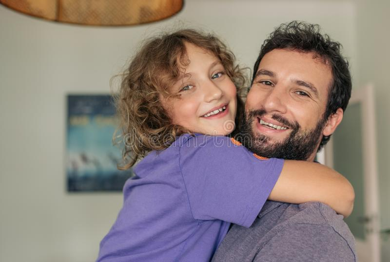 Paizinho satisfeito que guarda seu filho em seus braços em casa imagem de stock royalty free