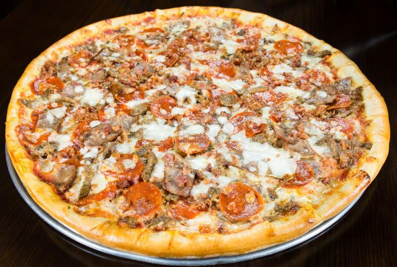 Paj för pizza för korvpeperonibacon hel på metalluppläggningsfatet royaltyfri bild