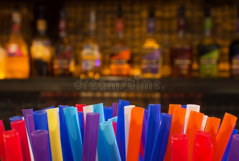 Paja colorida y botellas borrosas de bebidas espirituosas y licor en la barra imagen de archivo libre de regalías