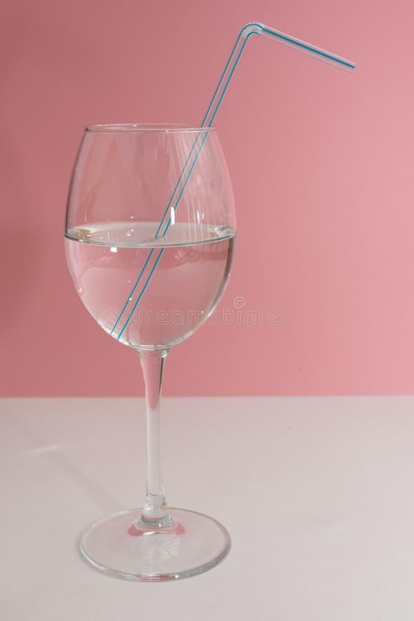 Paja de beber azul en la copa de vino llena con agua en la tabla blanca y el cierre rosado del fondo para arriba Espacio de la co imagen de archivo