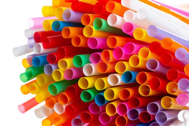 Paja plástica colorida en el fondo blanco imagenes de archivo