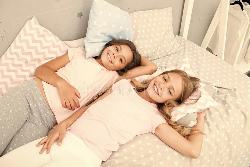 Pajama party and friendship. Sisters happy small kids relaxing in bedroom. Friendship of small girls. Leisure and fun. Having fun with best friend. Children stock photo