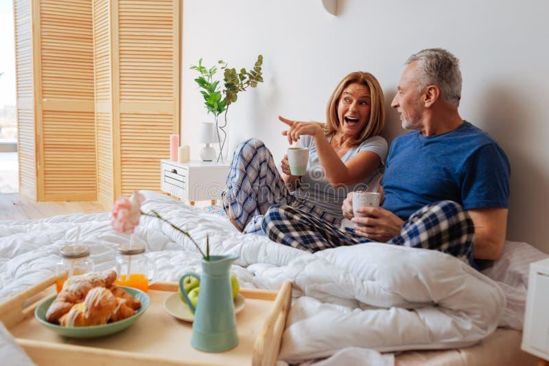 Couple wearing pajama trousers having breakfast in bedroom. Pajama trousers. Couple wearing squared pajama trousers having yummy breakfast in bedroom stock image