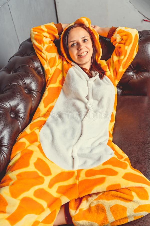 Pajamas for Halloween in the form of a giraffe. Emotional portrait of a girl on a sofa background. Crazy and funny man in a suit. stock photo