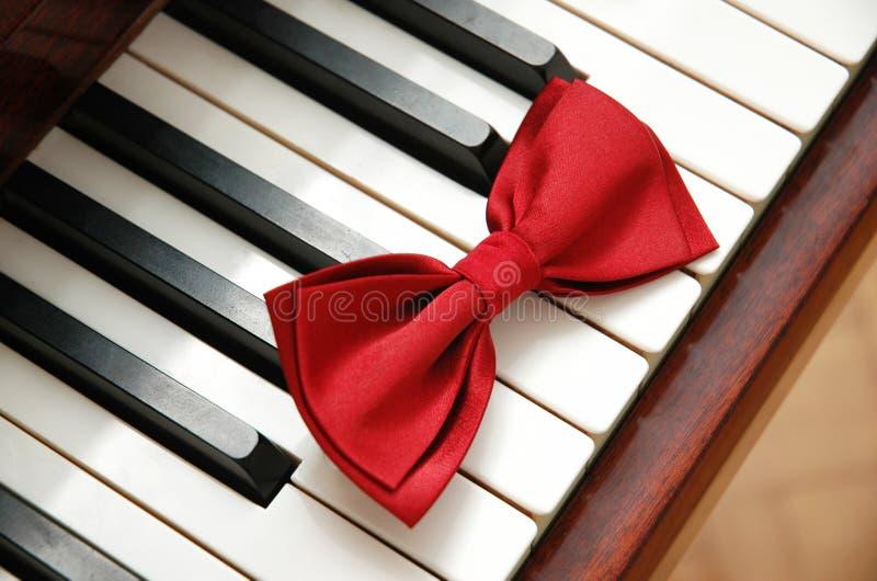 Pajarita roja en los claves del piano foto de archivo libre de regalías