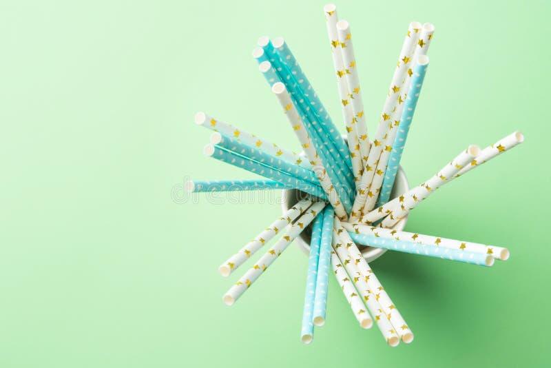 Pajas de beber del papel blanco y azul del cumpleaños con el modelo de lunar de oro de la estrella en tazas apiladas en verde Bas foto de archivo