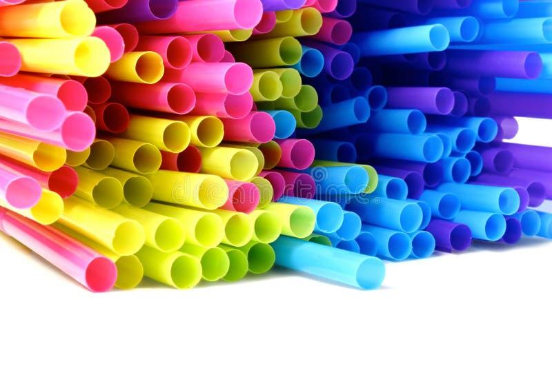 Pajas de beber plásticas coloreadas en el fondo blanco imagenes de archivo