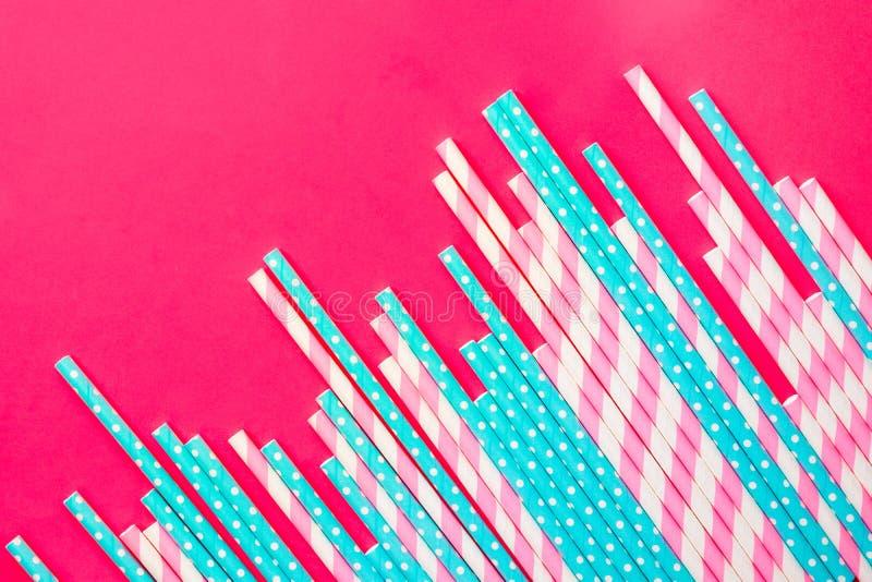 Pajas de beber rayadas del rosa y blanco del lunar del papel azul en fondo magenta Celebración de la fiesta de cumpleaños de los  imágenes de archivo libres de regalías