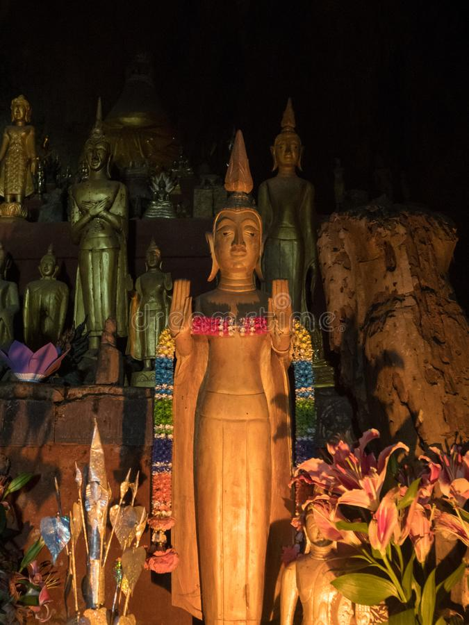 Hundreds of Buddha images in Pak Ou Caves. Luang Phabang, Laos, Asia. Buddha statues lit by candlelight in Pak Ou Caves overlook the Mekong River near the mouth royalty free stock images