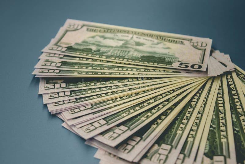 Pak van vijftig die dollarsbankbiljetten op blauwe achtergrond worden geïsoleerd